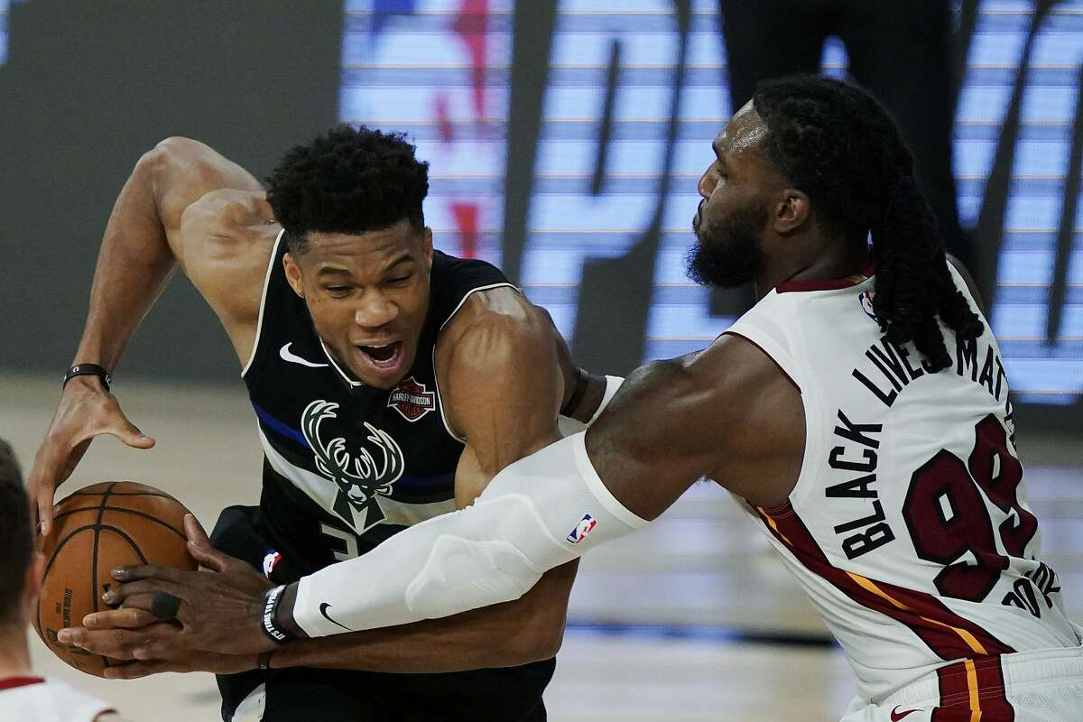 Miami Heat's Jae Crowder (99) knocks the ball loose from Milwaukee Bucks' Giannis Antetokounmpo (34), left, during the second half of an NBA conference semifinal playoff basketball game Wednesday, Sept. 2, 2020, in Lake Buena Vista, Fla. (AP Photo/Mark J. Terrill)