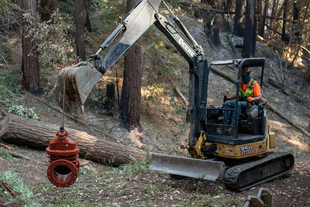 Jerry Cunha from San Jose based underground utility construction company Lewis and Tibbits Inc. moves a new value to replace a damaged one on a San Lorenzo Valley Water District tank after the CZU Lightning Complex Fire destroyed some of the infrastructure in Boulder Creek on Sept. 3, 2020.
