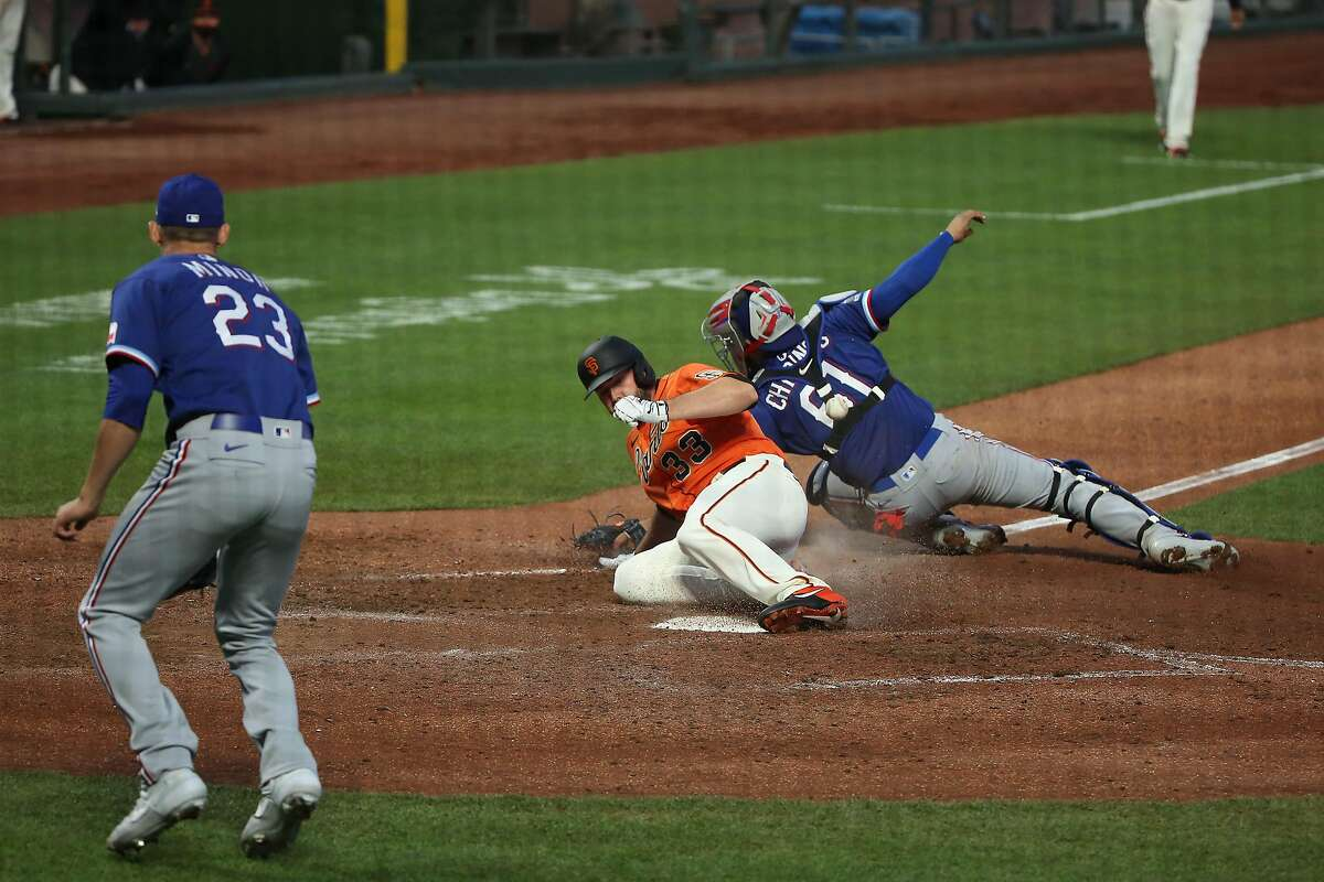 San Francisco Giants Darin Ruf slide into home base past Texas Rangers catcher Robinson Chirinos as the San Francisco Giants play the Texas Rangers during MLB game at Oracle Park on Friday, July 31, 2020 in San Francisco, Calif.