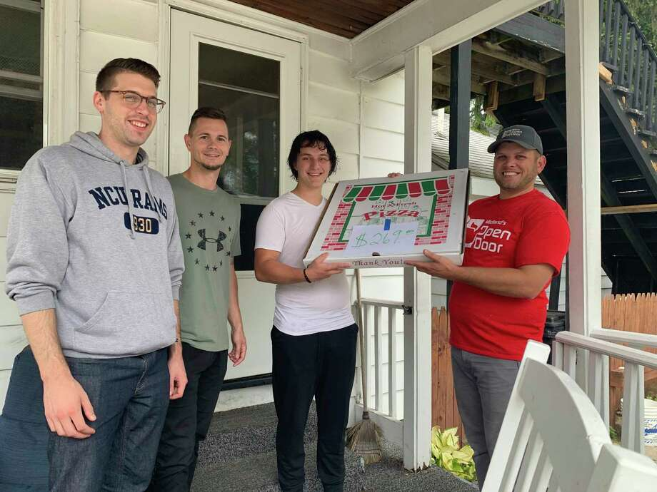 Nathan Ames returned 2,690 bottles, raising $269 for Midland's Open Door. On Sept. 1, Open Door staff, joined by Ames's youth pastors, Karl Sorget and Jake Singer, surprised him on his front doorstep with a monster meat lover's pizza from Pizza Dude. (Photo provided)