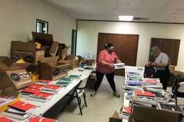 Volunteers from First Presbyterian Church of Alvin fill backpacks with school supplies, preparing them for students in Pearland and Alvin ISDs.