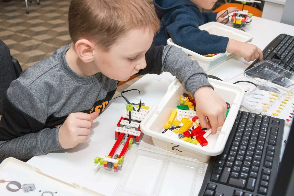 A student uses Legos for a lesson with NextGen SmartyPants in Canton, an educational center that focuses on STEAM education.