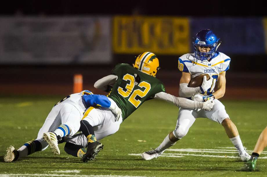 Midland High's Eli Gordon (right) tries to evade the grasp of Dow High's Garrett Daniels during an Oct. 25, 2019 game. Photo: Daily News File Photo