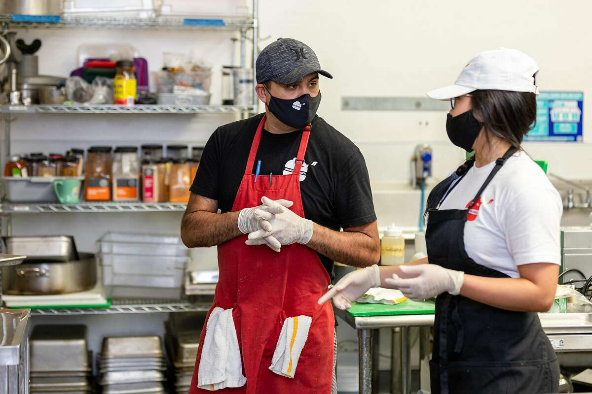 Bua Vanitsthian (right), owner of Chicken as Cluck, speaks with Eduardo Soto, kitchen manager, at Chicken as Cluck�s kitchen on Wednesday, May 20, 2020, in San Francisco, Calif.