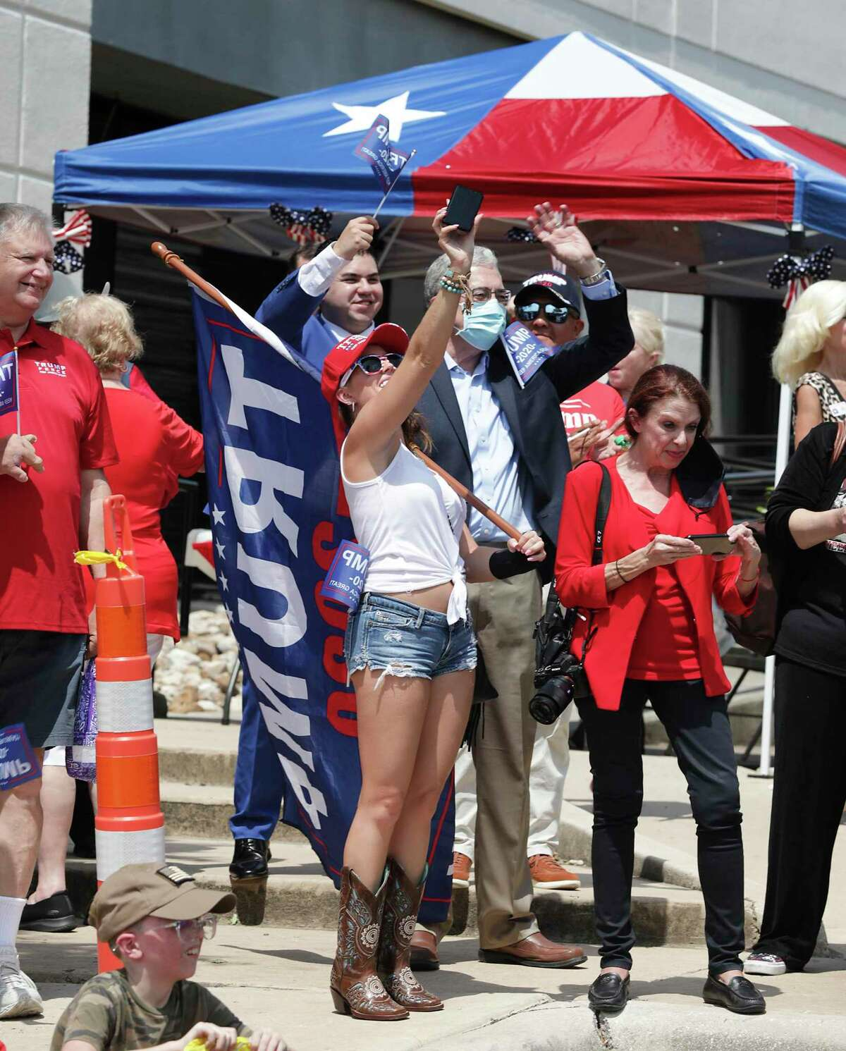 Trump supporters including Alex Ivko, center, greet his campaign bus at a stop in north San Antonio. Lt. Gov. Dan Patrick, former Trump campaign manager Brad Parscale and others are on the bus tour along Interstate 35.