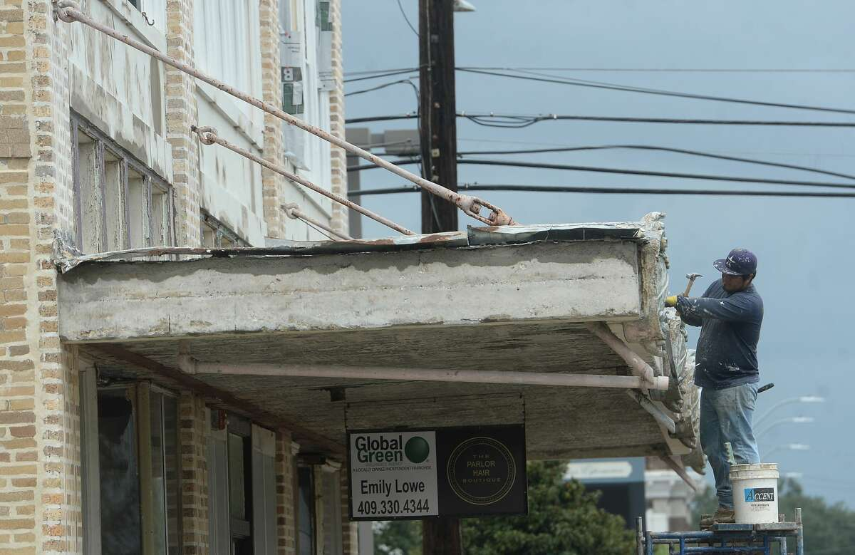 A worker removes damage from the awning of a historic building on N. 5th in Orange a week after the area was hit with some of the most severe damage in Southeast Texas by Hurricane Laura. Photo taken Thursday, September 3, 2020 Kim Brent/The Enterprise