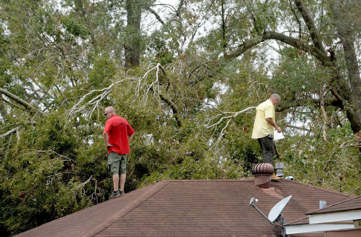 Insurance adjusters Donnie Hallman (left) and Johnny Hancock survey the roof of a home in Orange where a tree crashed above the garage as work continues a week after the area was hit with some of the most severe damage in Southeast Texas by Hurricane Laura. Photo taken Thursday, September 3, 2020 Kim Brent/The Enterprise