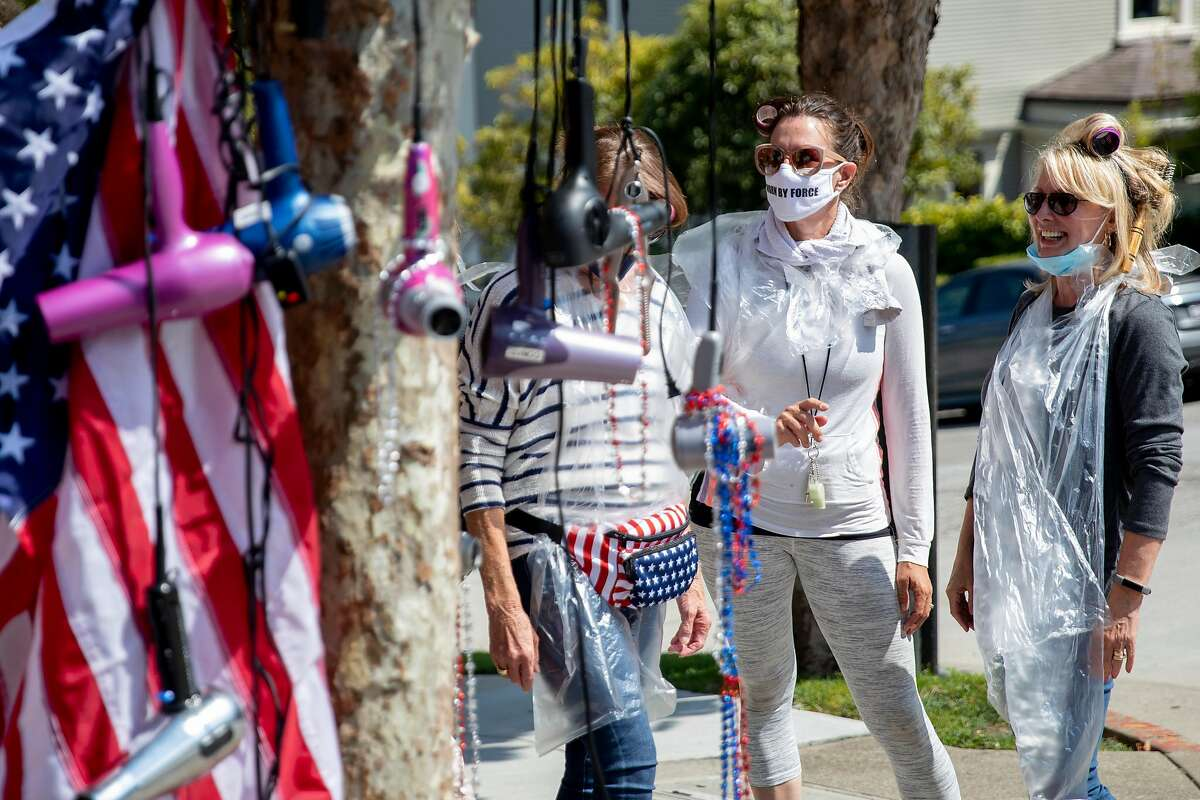 Protesters tie hair dryers and an American flag to a tree while gathered outside the home of Speaker Nancy Pelosi in San Francisco, Calif. Thursday, September 3, 2020. Demonstrators expressed outrage over the six-month closure of personal service businesses such as hair and nail salons after a video surfaced showing Nancy Pelosi getting her hair done indoors at a San Francisco salon without a mask.