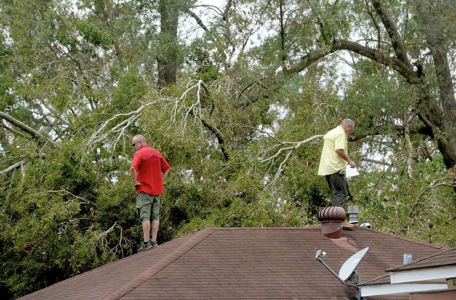 Insurance adjusters Donnie Hallman (left) and Johnny Hancock survey the roof of a home in Orange where a tree crashed above the garage as work continues a week after the area was hit with some of the most severe damage in Southeast Texas by Hurricane Laura.