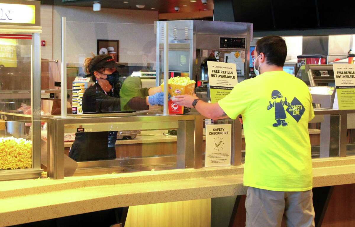 A moviegoer gets popcorn from employee Cierra Alvarado at Cinemark Theater in North Haven, Conn. on Thursday Sept. 3, 2020. It doesn't really sound like
