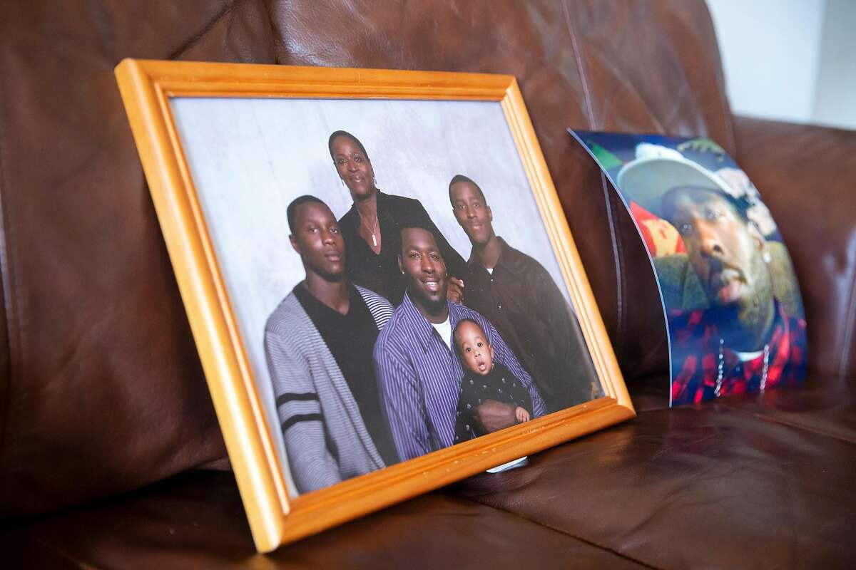 A family portrait of Steven Taylor, his son, two brothers and his mother sits on Addie Kitchen's couch at her home in Vallejo, Calif. on Thursday, September 3, 2020. Kitchen's grandson, Steven Taylor was shot on April 18, 2020 by a San Leandro police officer inside of a Walmart store. Recently the police officer involved in the shooting was charged with voluntary manslaughter for Taylors death.