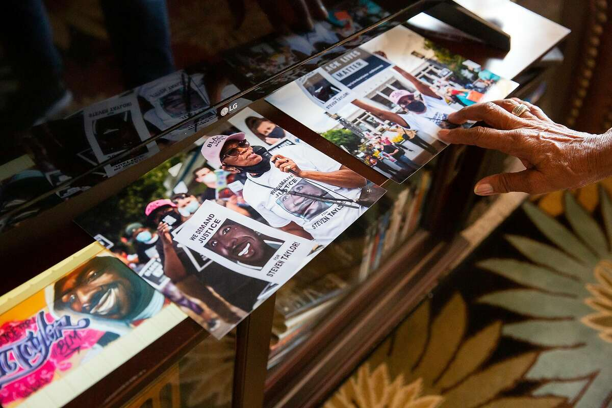 Addie Kitchen points to photographs of herself at the Justice for Steven Taylor protest that are laid out at her home in Vallejo, Calif. on Thursday, September 3, 2020. Kitchen's grandson, Steven Taylor was shot on April 18, 2020 by a San Leandro police officer inside of a Walmart store. Recently the police officer involved in the shooting was charged with voluntary manslaughter for Taylors death.