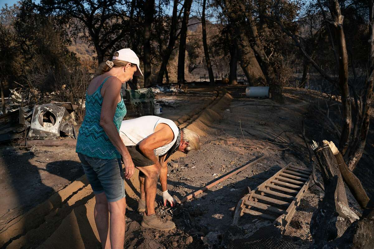 """Cindy Carrigan, 69, left, and Jim Campbell, 68, walk through Campbell's property that was destroyed by the Hennessey Fire on Pleasants Valley Road in Vacaville, Calif. on Thursday, Sept. 3, 2020. """"We didn't have time to grab anything,"""" said Campbell. """"The fire came too fast."""""""