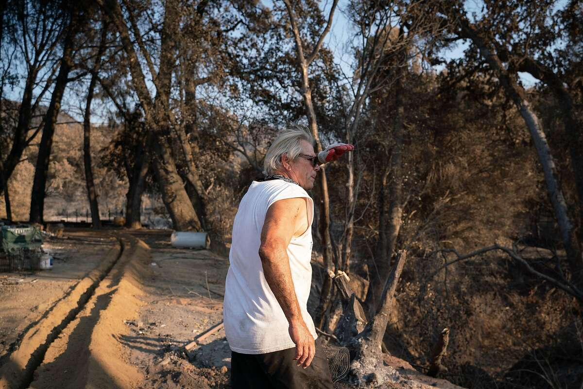 """Jim Campbell, 68, walks through his property that was destroyed by the Hennessey Fire on Pleasants Valley Road in Vacaville, Calif. on Thursday, Sept. 3, 2020. """"None of our animals were hurt and that is a miracle,"""" said Campbell who has lived at the property for over 12 years."""