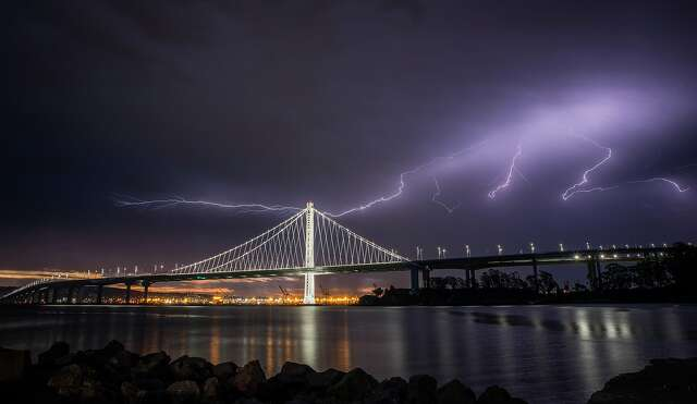 """Lightning illuminates the sky over the eastern span of the Bay Bridge as a storm passed through the area on Sunday morning in San Francisco, Calif., on Sunday, August 16, 2020. The rare """"lightning siege"""" sparked hundreds of wildfires across the Bay Area."""