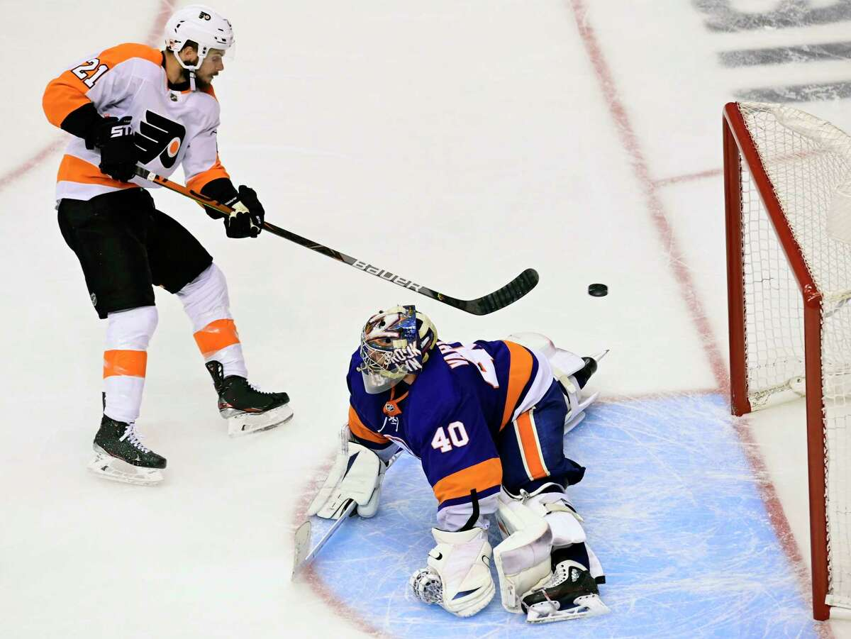 Philadelphia Flyers center Scott Laughton (21) scores against New York Islanders goaltender Semyon Varlamov (40) to tie the game during third-period NHL Stanley Cup Eastern Conference playoff hockey action in Toronto, Thursday, Sept. 3, 2020. (Frank Gunn/The Canadian Press via AP)