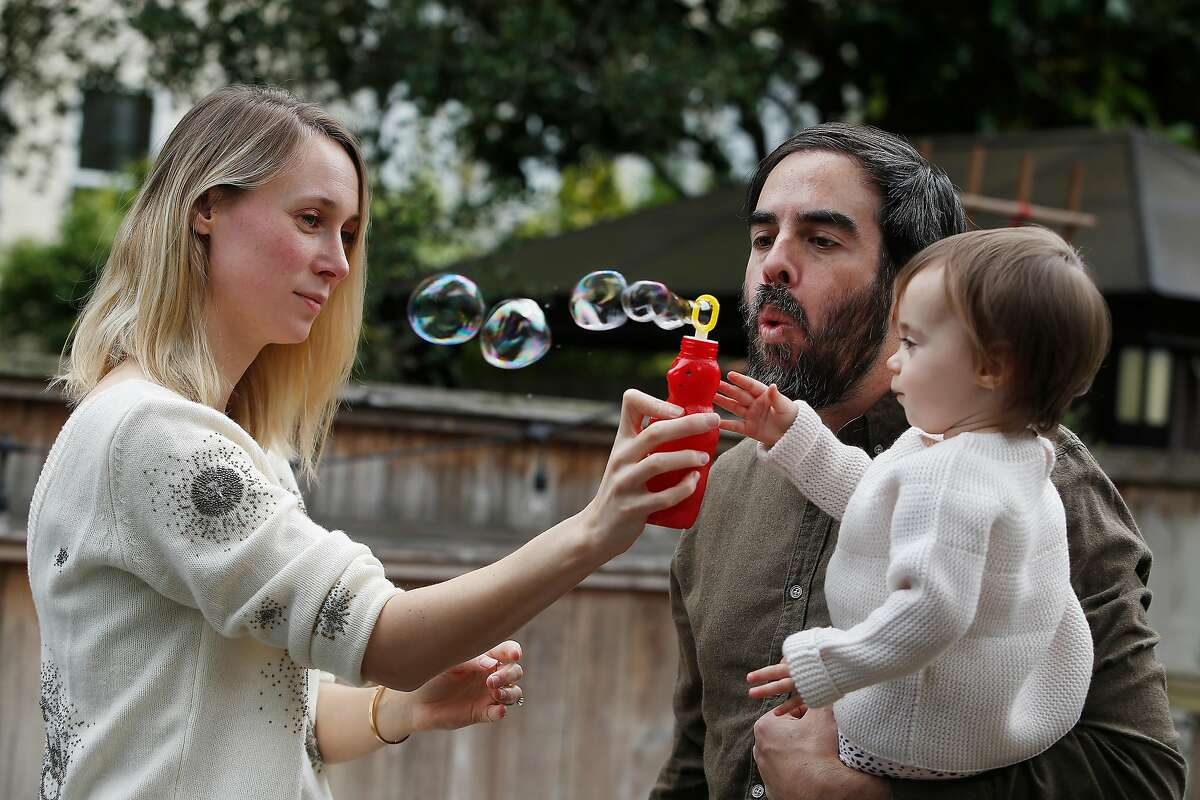 Michael Beckmann (center), co-founder CareVillage, blows bubbles for daughter Wyatt Beckmann (right), 1, as he and Eline van der Gaast (left), co-founder CareVillage play with their daughter in their backyard on Wednesday, September 2, 2020 in San Francisco, Calif.