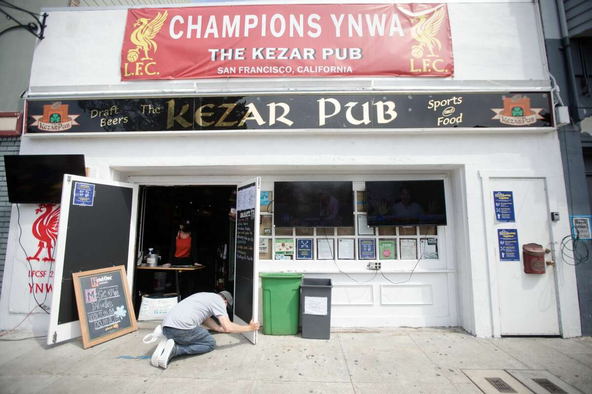 Customer Richie McAllister helps put a wedge underneath the door of the Kezar Pub on Sept. 3, 2020 in San Francisco, California.