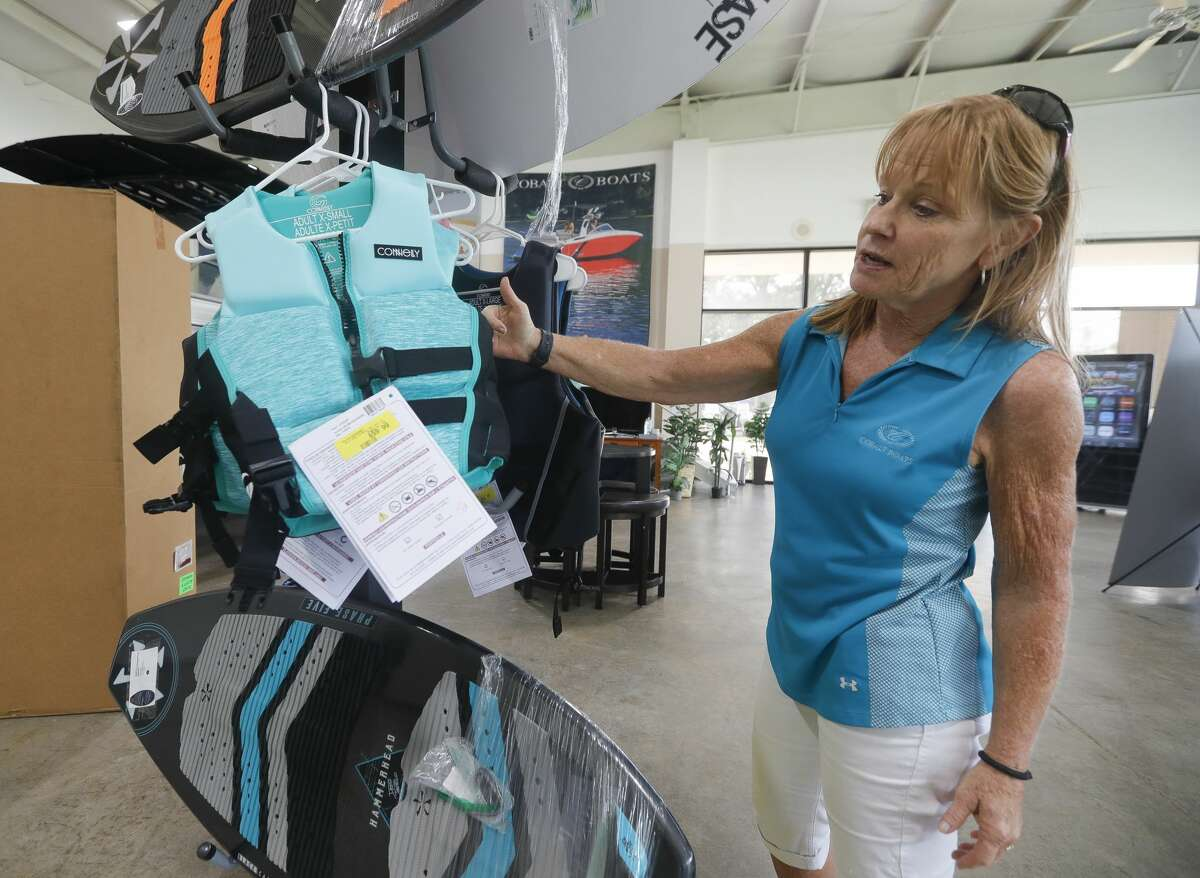 Melanie Clement, general manager at Rinkers Boat World at Lakeshore, shows some of the various life jacket options aviable to customers, Thursday, Sept. 3, 2020, in Montgomery. With all of this year's drowning victims on Lake Conroe not wearing life jackets to date, Montgomery County law enforcement and vendors continue to urge lake visitors to wear safety vests.