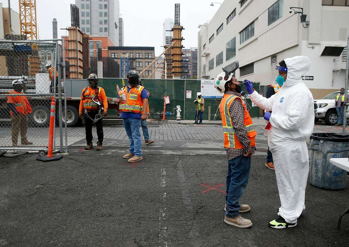 Armando Vidrio (right) collects a sample from a construction worker during weekly on-site coronavirus testing for Build Group employees and workers constructing a 302-unit residential building at 434 Minna Street in San Francisco, Calif. on Thursday, Sept. 3, 2020.