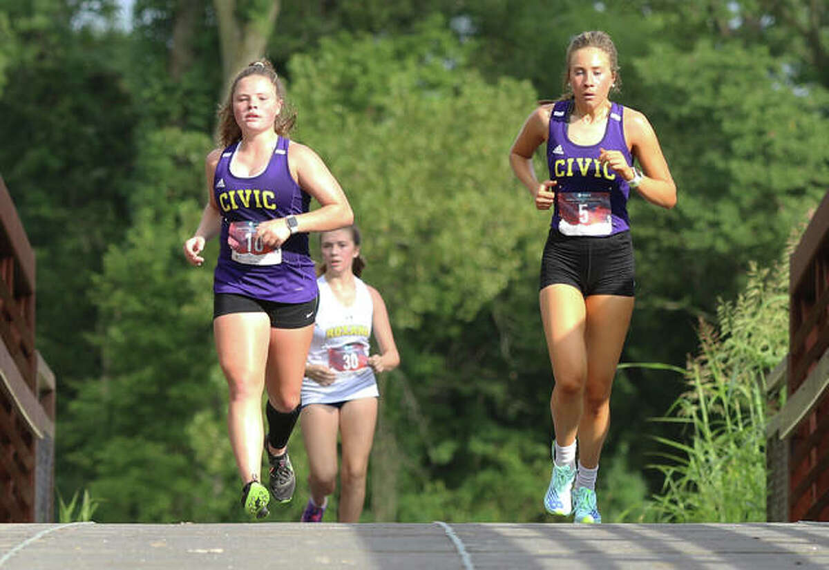 CM's Aubree Wallace (left) and Katie Hallstead cross the bridge midway through their season-opening cross country race at the Bethalto Sports Complex on Aug. 26. They are followed by Roxana's Mariah Carlisle.