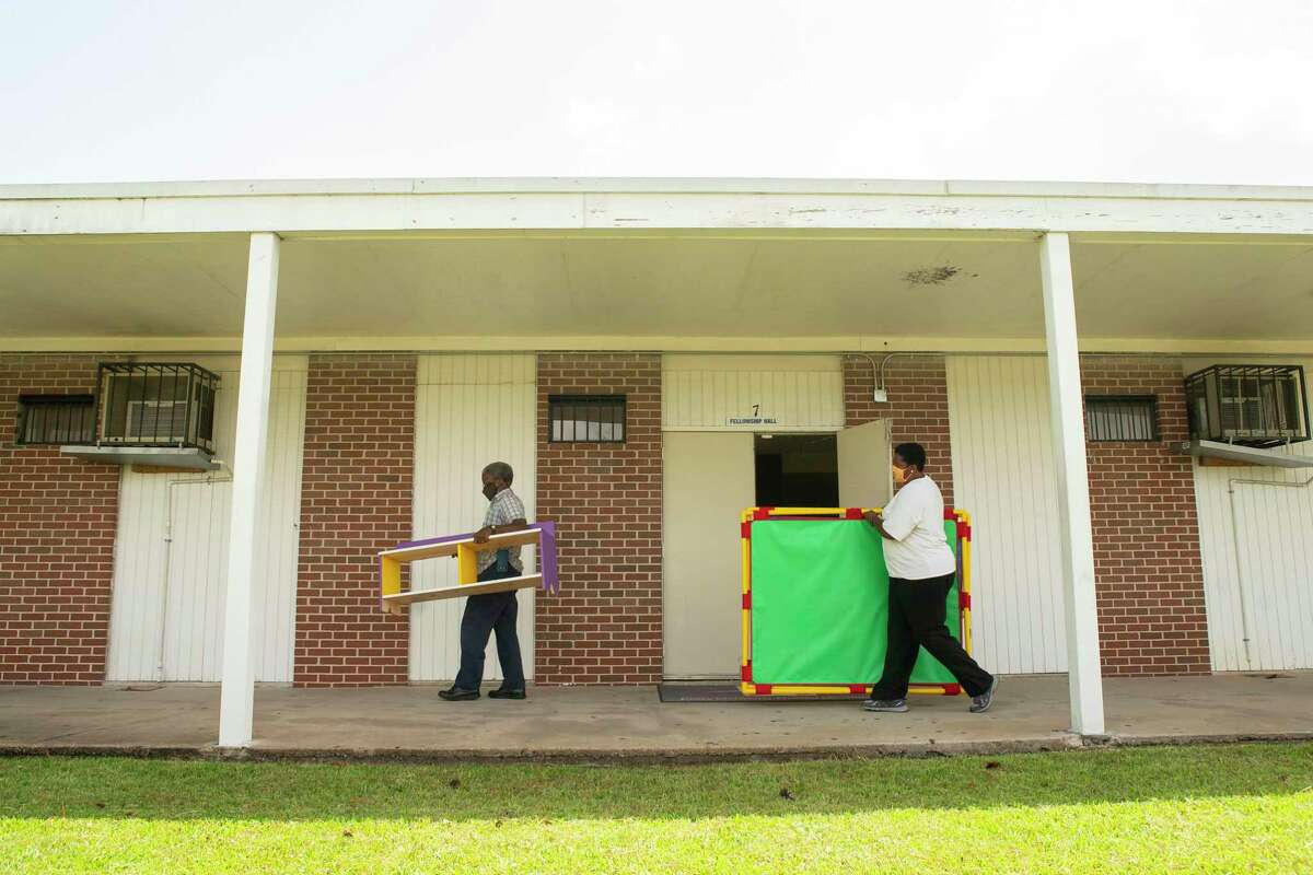 Volunteer Charles Cave and executive pastor Enid Henderson carry pieces of furniture into a classroom, Tuesday, Sept. 1, 2020, at Jones Memorial United Methodist Church's Crestmont Park campus in Houston. The church is partnering with HISD this fall to provide space for students to learn with church volunteers and HISD staff.