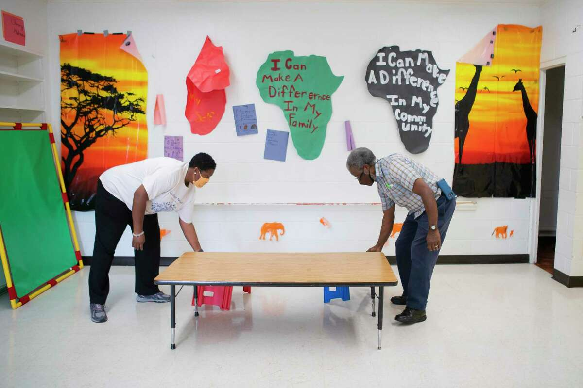 Executive Pastor Enid Henderson and volunteer Charles Cave place furniture in a classroom, Tuesday, Sept. 1, 2020, at Jones Memorial United Methodist Church's Crestmont Park campus in Houston. The church is partnering with HISD this fall to provide space for students to learn with church volunteers and HISD staff.