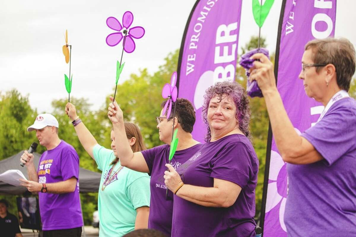 Julie Harvey stands among other people who also lost a relative or friend to Alzheimer's. Julie's father, Paul, passed away at age 85.