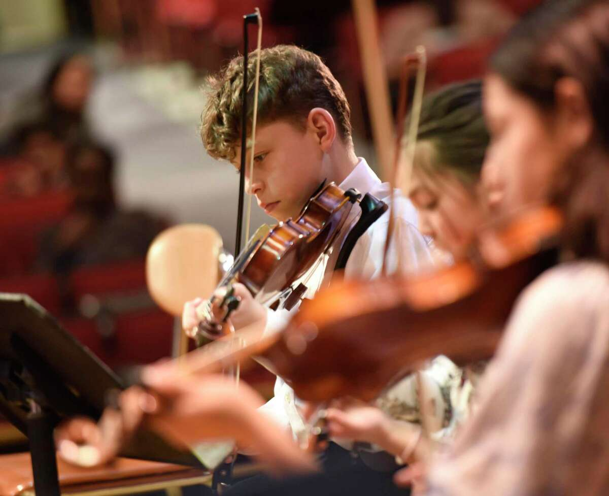 Sebastian Osorio, 12, plays violin on stage during Greenwich Alliance for Education's Tuning In To Music free lesson at Western Middle School in Greenwich, Conn. Tuesday, April 19, 2018.