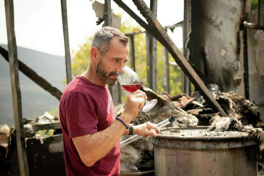 La Borgata Winery owner Gerry Iulano sniffs wine from a burned barrel amidst the charred remains of his winery during the LNU Lightning Complex fire in Vacaville, California on Aug. 23. Firefighters battled some of California's largest-ever fires that have forced tens of thousands from their homes and burned one million acres. Ron says California wine country is shrouded with the smoke of raging forest fires which cancel out the wonderful bouquets of the grapes with a stank odor of fire soot. Photo: JOSH EDELSON, Contributor / AFP Via Getty Images / AFP or licensors