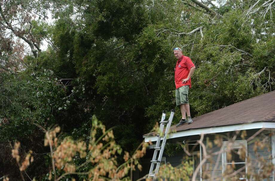 Insurance adjuster Donnie Hallman surveys the roof of a home in Orange where a tree crashed above the garage as work continues week after the area was hit with some of the most severe damage in Southeast Texas by Hurricane Laura. Photo taken Thursday, September 3, 2020 Kim Brent/The Enterprise Photo: Kim Brent / The Enterprise / BEN