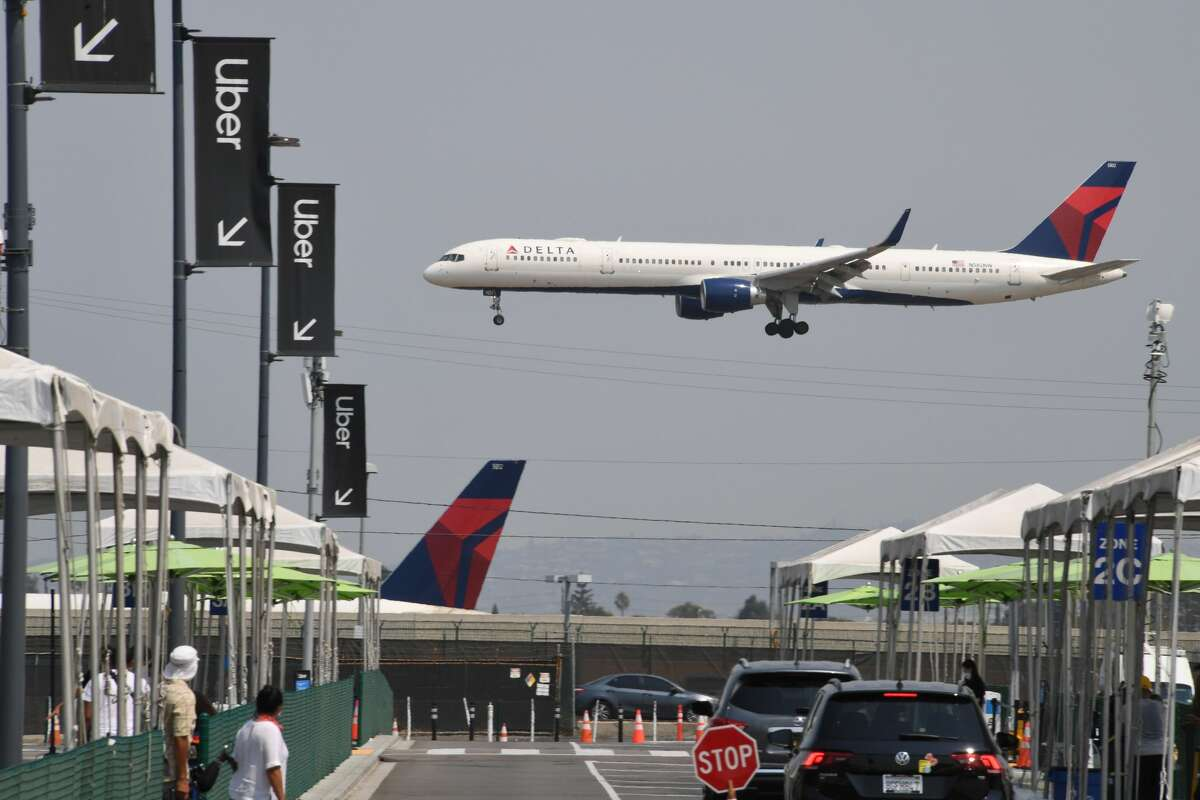 A Delta Airline plane passes Uber signs at the ride share pick up and drop off area as it comes in for a landing August 20 at Los Angeles International Airport in Los Angeles, California.