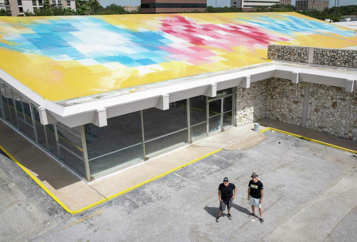 """Rick Williams, left, founder and CEO of Joyride, and Sebastien """"Mr D 1987"""" Boileau pose for a photo next to a mural Boileau painted on Williams' building Wednesday, Sept. 2, 2020, in Houston."""