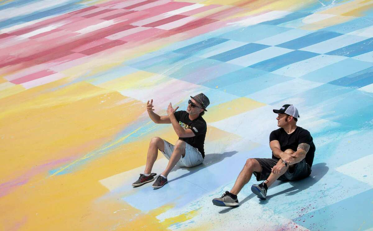 """Sebastien """"Mr D 1987"""" Boileau, left, and Rick Williams, founder and CEO of Joyride, talk on the roof of Williams' building, where Boileau painted a large mural, Wednesday, Sept. 2, 2020, in Houston."""