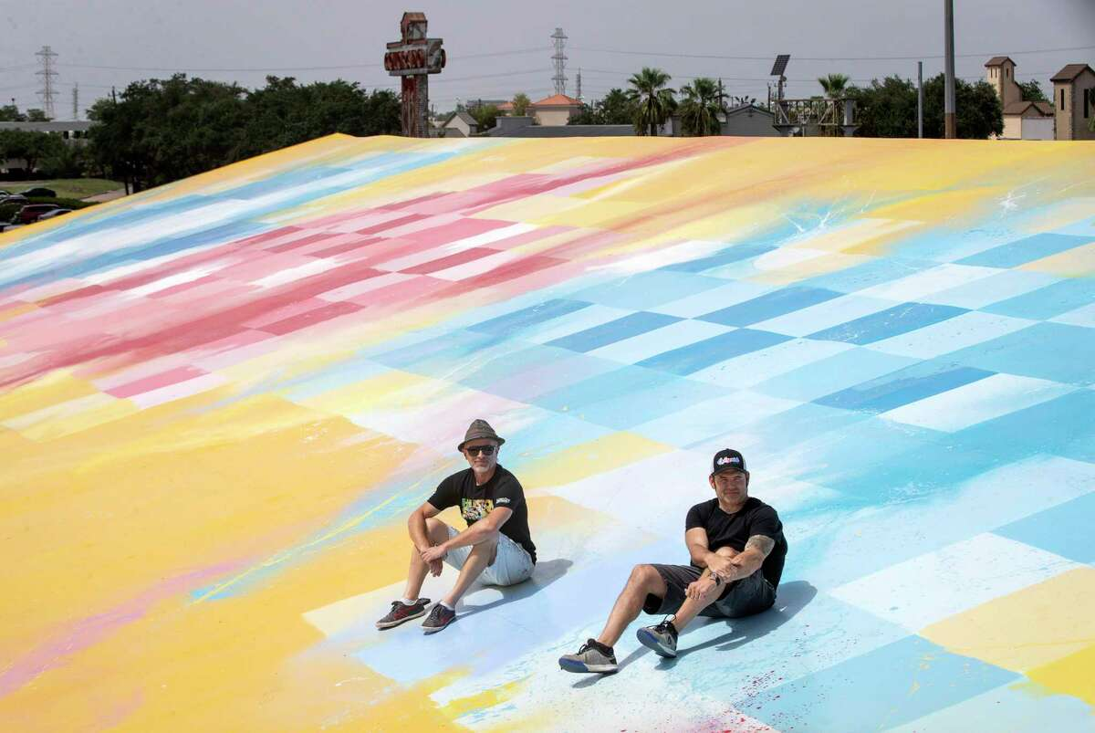 """Sebastien """"Mr D 1987"""" Boileau, left, and Rick Williams, founder and CEO of Joyride, pose for a photo on the roof of Williams' building, where Boileau painted a large mural, Wednesday, Sept. 2, 2020, in Houston."""
