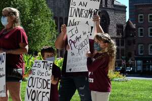 Lansingburgh School District students Noah, left, and Madison Trotter, 8, right, attend a rally calling on Gov. Cuomo to restore school funding recently cut by the state on Friday, Sept. 4, 2020, during a demonstration at the Capitol in Albany, N.Y. Noah is a pre-k student and Madison is starting third grade through distance learning. Madison said she would rather be back in a school classroom. (Will Waldron/Times Union)