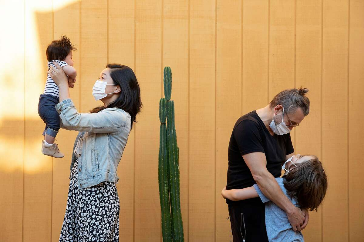 Deborah Tu, left, holds up her son Andre, 3 months, while Joey Jelenik, right, hugs his son Jax, 6, at Tu�s home in San Francisco, Calif., Thursday, Sept. 3, 2020. Tu and Jelenik are the founders of NurturePods.org which matches families with pandemic learning pods.