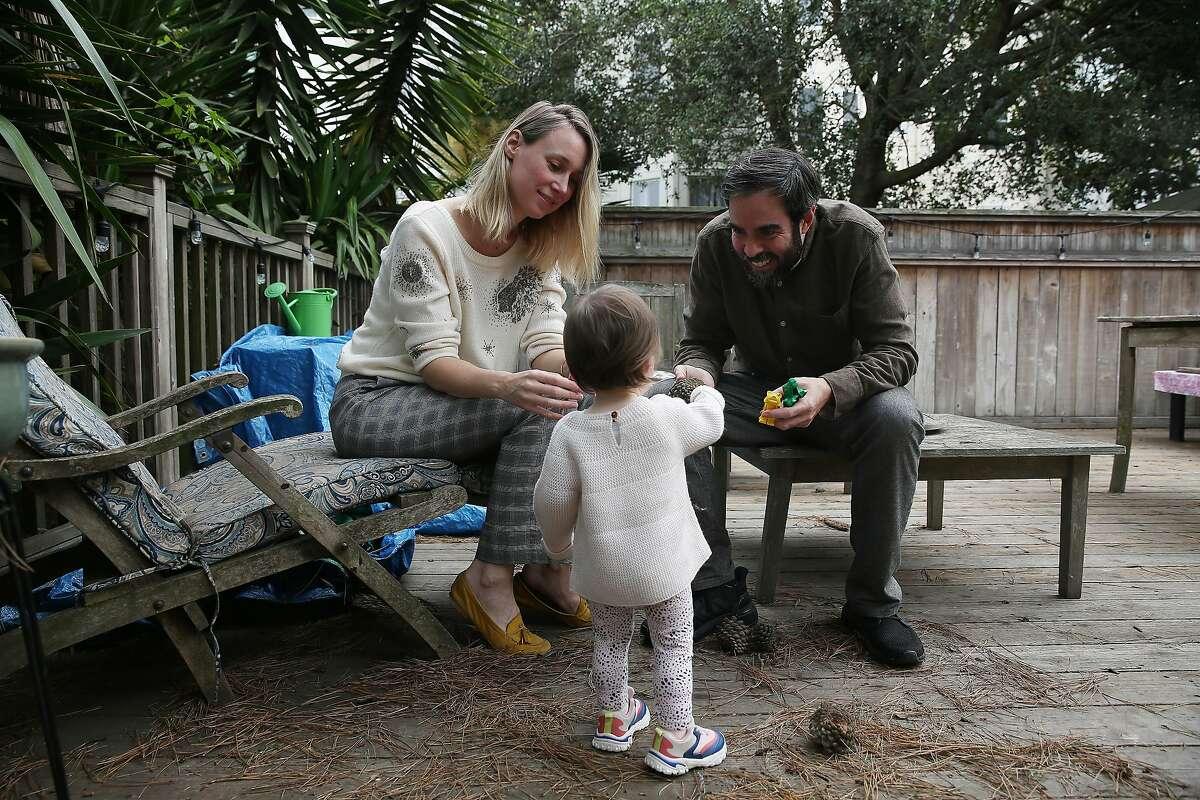 Eline van der Gaast (left), co-founder CareVillage, and Michael Beckmann, co-founder CareVillage, play with their daughter Wyatt Beckmann (center), 1, in their backyard on Wednesday, September 2, 2020 in San Francisco, Calif.