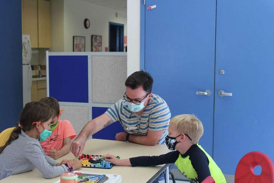 George Bennett, the New Canaan YMCA's Youth and Camp Y-Ki director with Remote Learning Day Family Support Program participants, plays a game of Trouble with campers on a day during the camp this summer. Craig Panzano, who is the executive director of the social services organization's town location, writes this letter about previous instances during the season when the New Canaan Community Foundation helped them out, and the support it continues to give them in the two organizations partnership. Photo: New Canaan YMCA / Contributed Photo