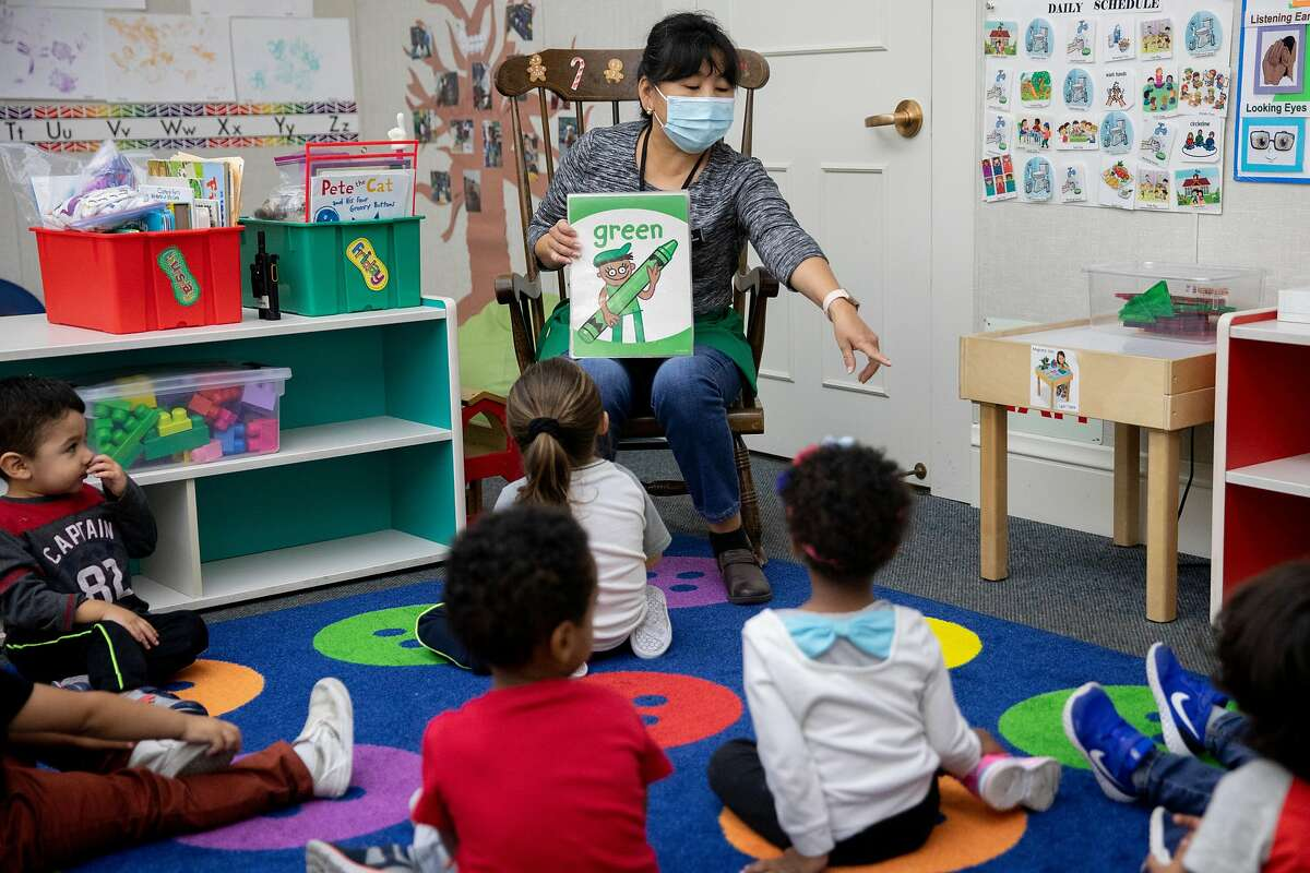Teacher Boyana Tseren-Ochir wears a mask while teaching students in a group circle to start their morning at Saint Vincent's Day Home in Oakland, September 3, 2020.