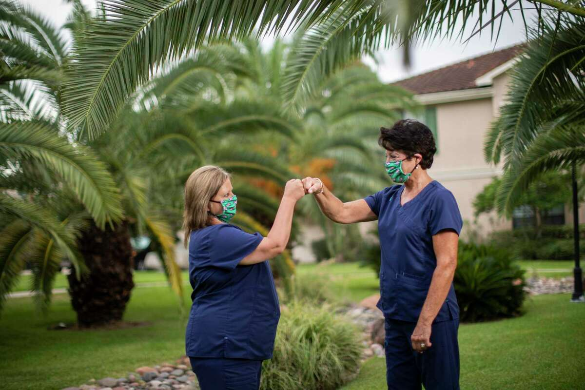 Registered nurses Jeannie Carr, left, and Rhonda Williams, right, fist bump Thursday in Clear Lake where they are currently living. The nurses came from Louisiana to help with COVID-19 in July, and hoped they could stay longer but their temporary Texas nursing license ends Monday.
