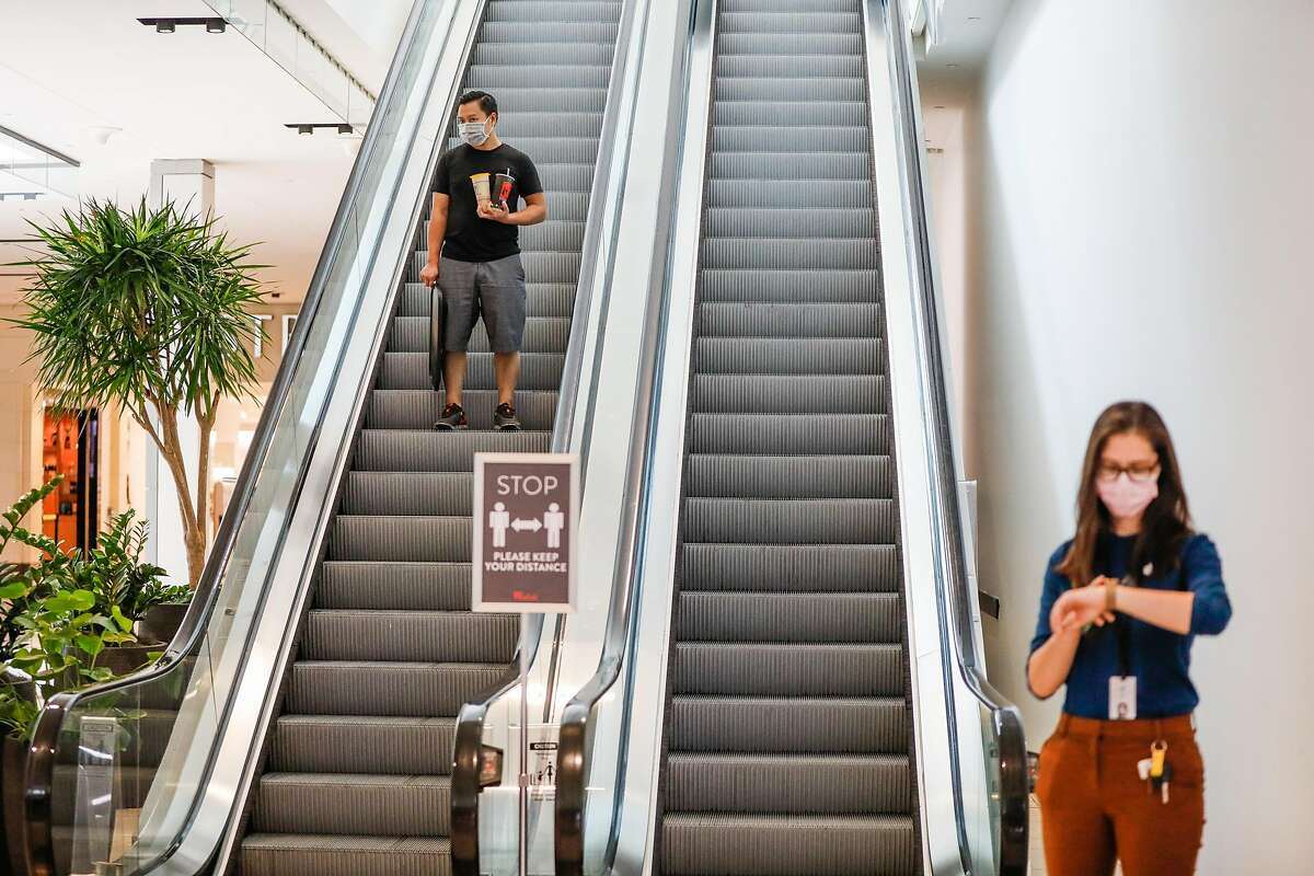 A man rides the escalator while shopping at Westfield Valley Fair Mall hours after it reopened following the COVID-19 global pandemic in San Jose, California, on Monday, Aug. 31, 2020.