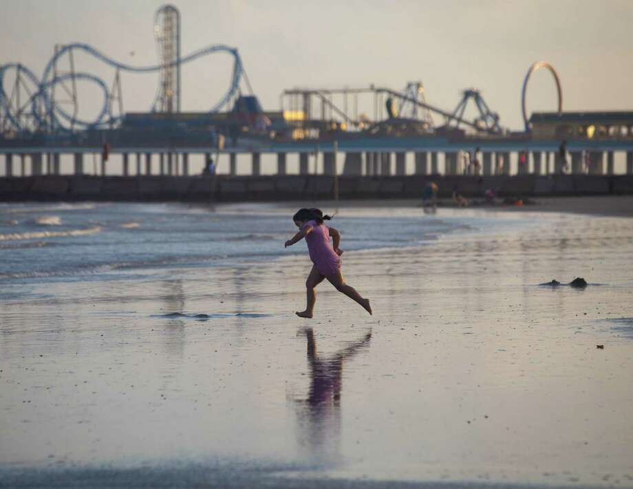 A young girl runs to the water fully clothed at Galveston Beach near the Pleasure Pier the evening of Thursday, July 30, 2020. Photo: Hadley Chittum, Houston Chronicle / Staff Photographer / © 2020 Houston Chronicle