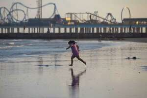 A young girl runs to the water fully clothed at Galveston Beach near the Pleasure Pier the evening of Thursday, July 30, 2020.