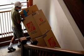 Movers gather Kristin Demoro's boxes from her packed-up apartment in Oakland, Calif. Tuesday, April 21, 2020. Demoro is moving to Washington state to be close to her mom after being laid off due to the Coronavirus outbreak and shelter-in-place, but she has a really extensive family history and lineage in San Francisco and never thought she'd leave. Her father, Harre Demoro, was a famed San Francisco Chronicle reporter, her grandfather was born in 1900 in San Francisco.