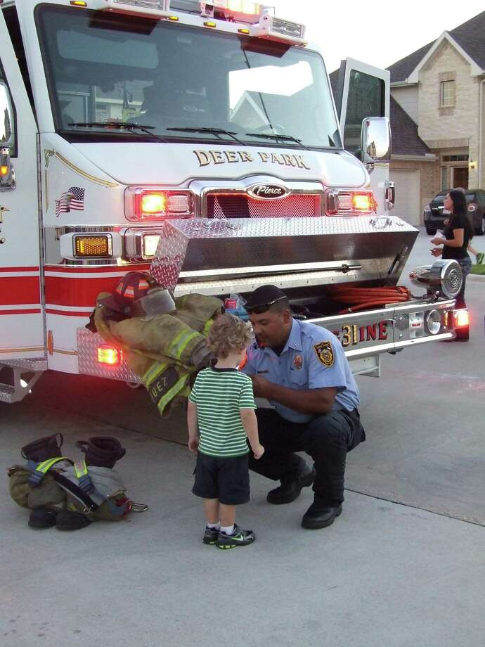 Deer Park Fire Department Station 3 Capt. Keith Vasquez pins a badge on a child during a previous National Night Out party. This year's event on Oct. 6 may look different because of the coronavirus pandemic, but the city is planning to participate. Photo: Jeri Martinez / Broadcaster / Broadcaster