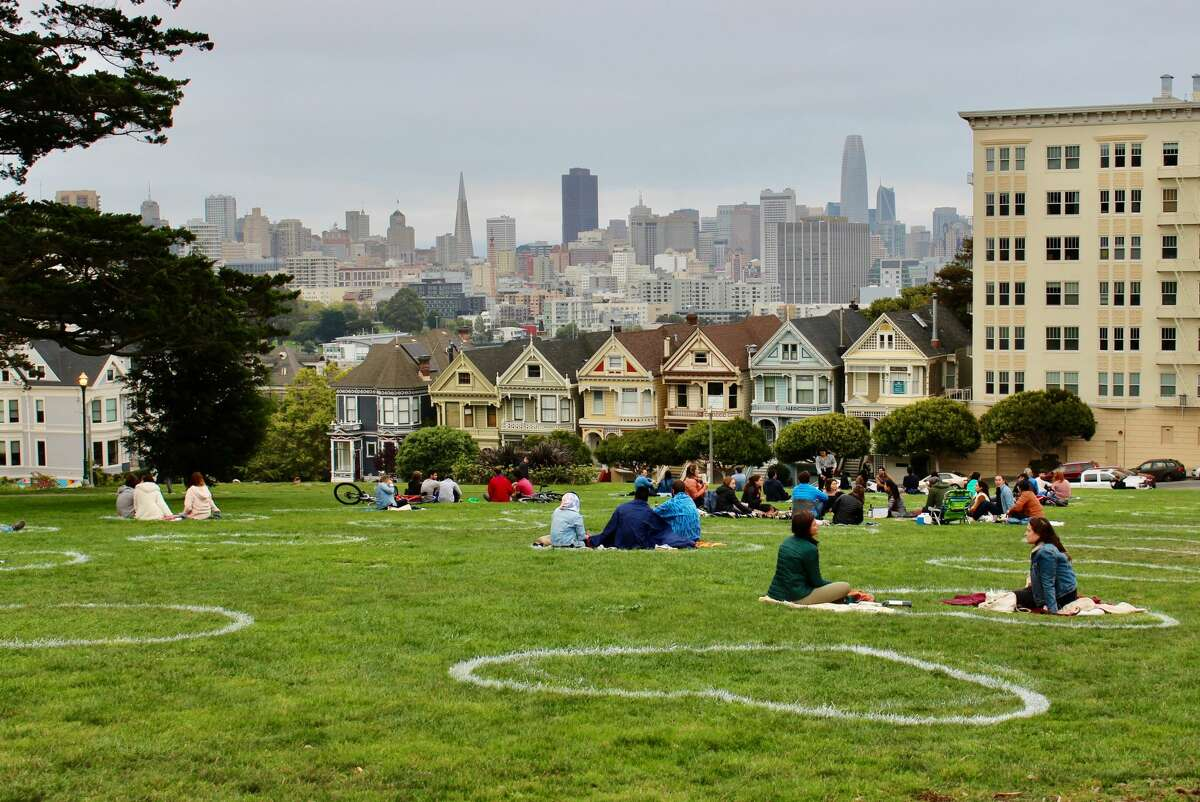 FILE: White chalk hearts keep people socially distant at Alamo Square in September 2020.