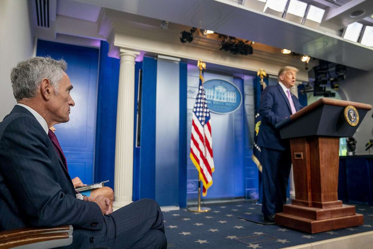 President Donald Trump, accompanied by Scott Atlas, senior fellow at the Hoover Institution, left, speaks at a news conference in the James Brady Press Briefing Room at the White House, Tuesday, Aug. 11, 2020, in Washington. (AP Photo/Andrew Harnik)