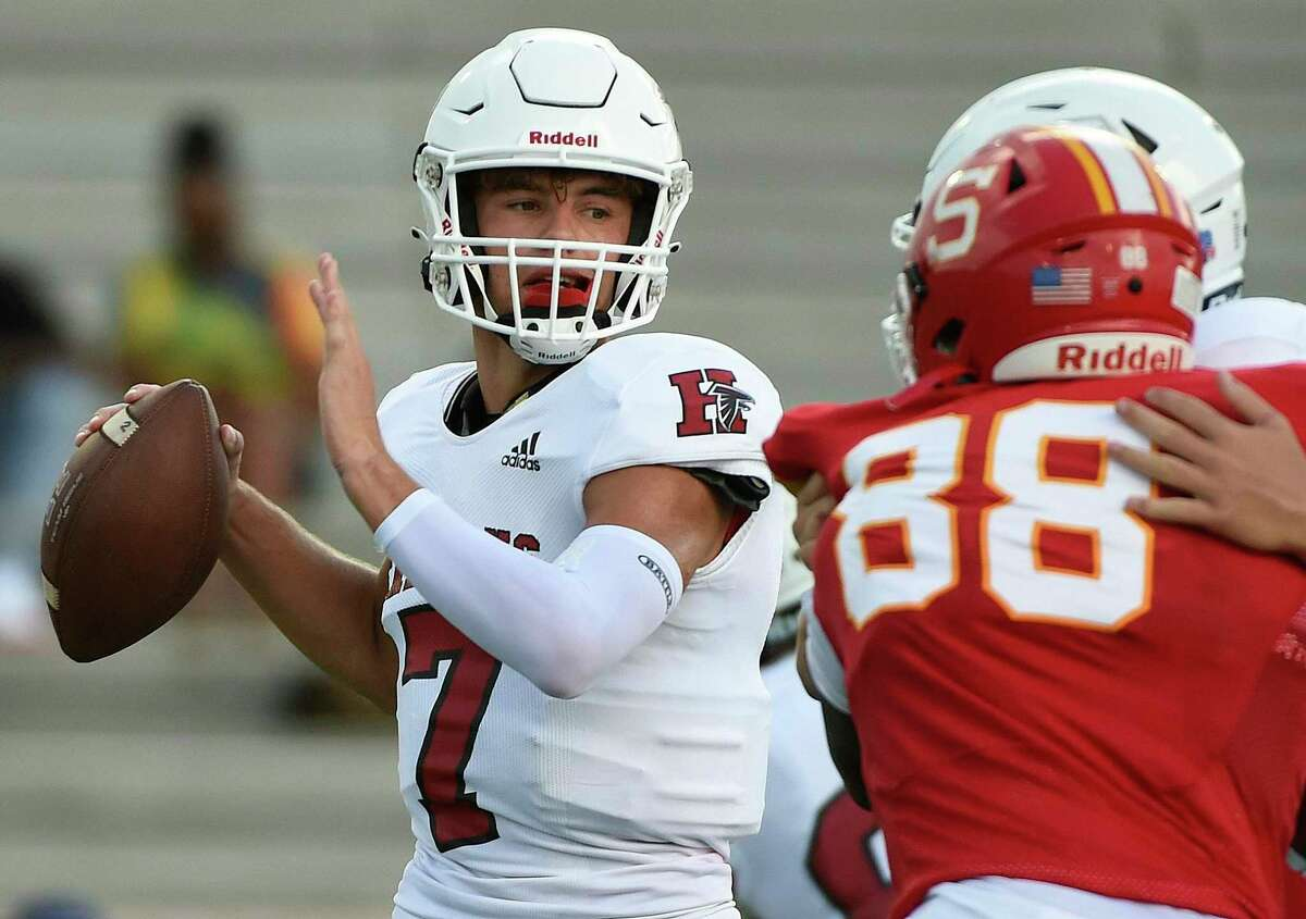 Huffman quarterback Luke Thomas, left, looks to pass during the first half of a high school football game against Stafford, Saturday, Aug. 29, 2020, in Stafford, TX.