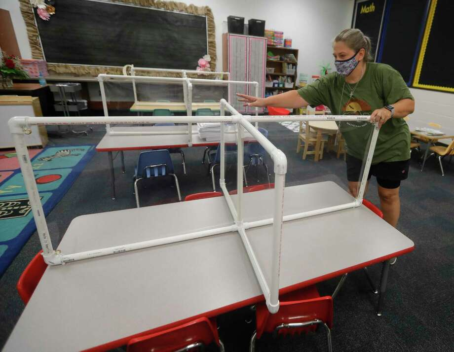 Counselor Lisa Durham helps move 60 lightweight safety dividers for classroom tables at Reeves Elementary School, Saturday, Aug. 15, 2020, in Conroe. Members of the Conroe Noon Lions Club constructed the dividers from PVC pipe, plexiglass and vinyl stretched across the middle to divide the table in two. Students who chose in-class instruction are set to return to campus on Sept. 8. Photo: Jason Fochtman, Houston Chronicle / Staff Photographer / 2020 © Houston Chronicle